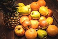 Tasty fruit background with orange, apples, pineapple and banana on the wooden boards table.