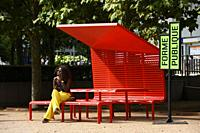 Woman sat on a red big bench at La Defense,Paris,France.