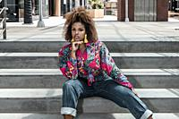 Confident young African American female with afro hairstyle and stylish earrings dressed in colorful shirt and jeans sitting on steps on city street a...