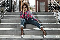 Low angle full body young African American female in stylish colorful shirt and jeans sitting on concrete stairs near modern city building and looking...