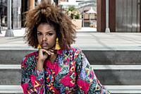 Modern young African American female with curly hairstyle wearing trendy shirt with colorful print and yellow tassel earrings looking at camera while ...