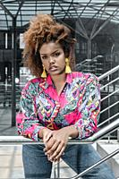 Serious millennial African American female with curly hair wearing trendy colorful shirt and jeans with yellow tassel earrings leaning on metal banist...