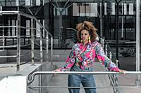 Young independent African American curly haired female with tassel earrings dressed in bright shirt with knot and jeans standing near metal railing ag...