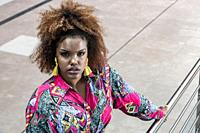 High angle of serious millennial African American female with afro hair wearing stylish colorful shirt and tassel earrings looking at camera while sta...