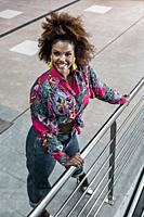 From above of cheerful youthful African American female in trendy jeans with colorful shirt and earrings standing near metal banister and looking at c...