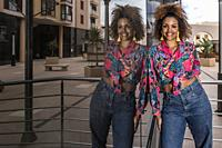 Positive millennial African American female in stylish colorful shirt with knot and trendy jeans standing near mirrored glass wall of modern city buil...
