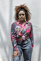 Young stylish African American female model with afro hairdo and bright tassel earrings wearing fashionable colorful shirt with knot and jeans looking...