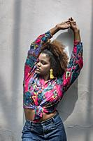 Young curly haired African American female in bright outfit and colorful earrings standing with arms raised against gray wall.