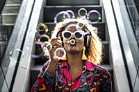 Stylish black lady in wireless headphones and earrings sitting on escalator with pout lips while blowing colorful transparent bubbles in back lit.