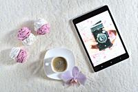 handmade marshmallows next Cup of coffee and a tablet with a picture of the camera.