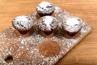 chocolate muffins with white icing lying on a Board sprinkled with powdered sugar.