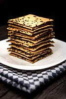 cookies with sunflower seeds and sesame seeds on a white plate with checkered napkin.