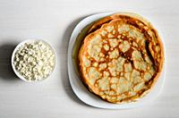 homemade pancakes on a white plate with cottage cheese.