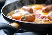 fried eggs with sausages and tomatoes on a hot pan, cooking breakfast.