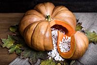 pumpkin lying on a wooden table with viburnum and seeds.