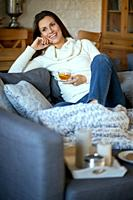 attractive young woman in sweater relaxes on a gray sofa at home and drinks tea with lemon.