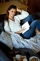 beautiful young brunette woman reading a book on a gray sofa.
