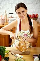 beautiful young woman, brunette slicing bread in the kitchen at a table full of organic vegetables.