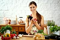beautiful young woman, brunette holds aubergine and tomato in the kitchen at a table full of organic vegetables.