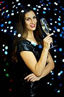 beautiful young smiling woman with one glass of champagne on a black background in New Year's Eve.