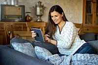 beautiful young smiling woman in white sweater sitting with a tablet on a gray sofa.