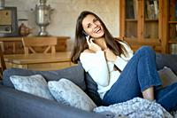 beautiful young smiling woman in white sweater talking on the phone on a gray sofa.