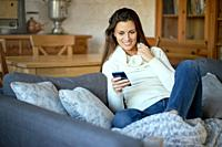 beautiful young smiling woman in white sweater texting on her phone on a gray sofa.