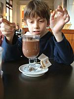 Young boy tastes frothy hot chocolate drink in a glass with chocolate sweet treat and signals perfection with his hands in the sunlit cafe of the Cinq...