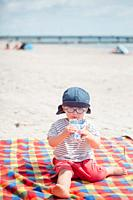 . 2 years old boy drinking juice at the beach.