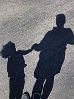 Shadow of man with child in the street.