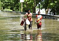 Villagers waking wade through a flooded road, in Morigaon district of Assam, Monday, July 13, 2020.