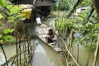 A resident uses a country boat to move across a flooded area in Morigaon district of Assam, Monday, July 13, 2020.