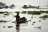 A woman move to safer place from a flooded area in Kamrup district of Assam, Monday, July 13, 2020.