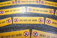 Singapore, Republic of Singapore, Asia - Yellow prohibition signs are seen on steps at a MRT station (subway station) that read Do Not Sit Here.