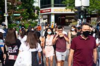 Singapore, Republic of Singapore, Asia - Pedestrians wearing a protective face mask walk along Orchard Road in the city centre after the reopening fol...