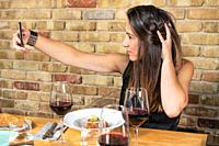Beautiful Young woman is taking a selfie photograph while eating in restaurant. High quality photo.