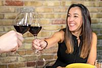 Close up of young couple toasting with glasses of red wine at restaurant. High quality photo.