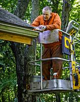 Worker age 72 on man lift, coating wood preservative on house trim, orange chain saw chaps are for tree work, safety clothing.