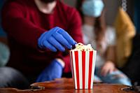 Couple wearing protection gloves and mask for Covid-19, coronavirus concept, date night in quarantine with red and white striped bucket with popcorn r...