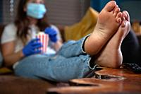 Woman wearing safety mask and gloves for Covid-19, coronavirus and quarantine watching television at home with red and white striped cupboard bucket w...