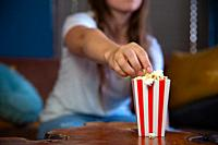 Beautiful young woman sitting on a living room couch, watching television with a red and white striped cardboard box with popcorn retro popcorn box mo...