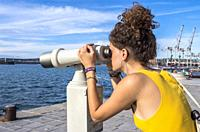 Girl looking through binoculars, Koper, Slovenia.