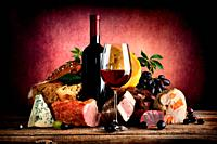 Red wine and different food on a wooden table.
