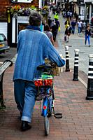 A Woman Pushes A Bicycle Through The High Street, Lewes, East Sussex, UK.