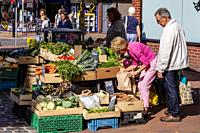 A Senior Couple Buying Vegetables From A Stall In The High Street, Lewes, East Sussex, UK.