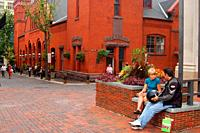 An adult couple chat on a brick bench outside the Central Market in Lancaster, Pennsylvania.