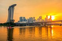 Singapore downtown with Sand Hotel, skyscrapers and two bridges. Golden sunset and beautiful night lighting.
