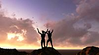 two man' s silhouette with her hands raised in the sunset.