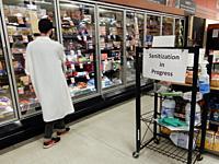 Supermarket Clerk Cleaning Freezer Cases, Wellsville, New York, USA.
