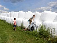 Boy and Girl Playing on Hay Bales, Alfred, New York, USA.